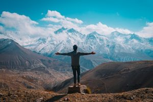 Beautiful blue mountain view with a person freely reaching out with open arms