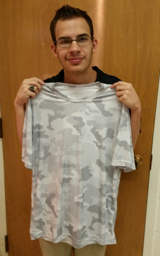 Joel Glover holding a sample of the new spirit wear shirts